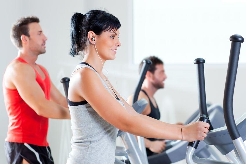 homem e mulher com elíptica elíptica no ginásio esportivo