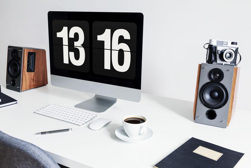 Close-up de um espaço de trabalho minimalista com um computador desktop e alto-falantes em uma mesa branca no interior de um escritório em casa moderno. Foto real