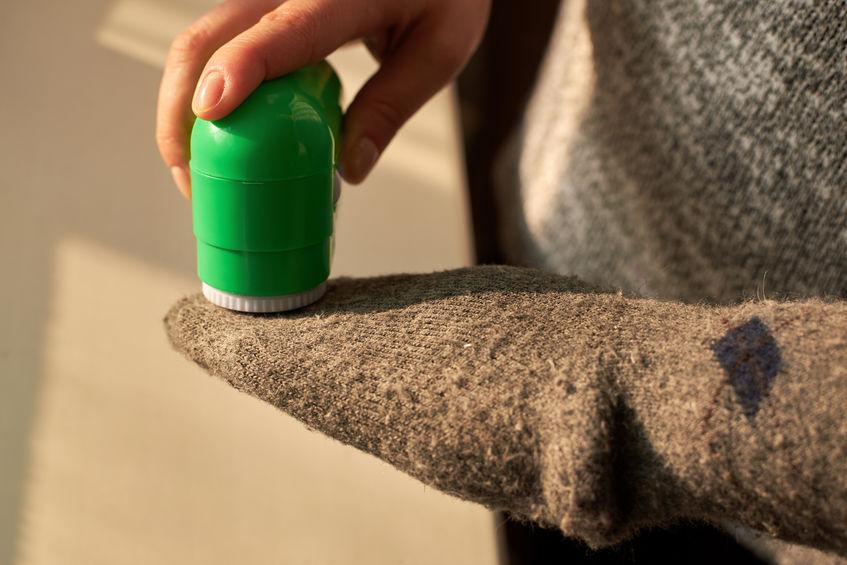 Mulher tira fiapos de meias de lã com a ajuda de uma máquina elétrica.