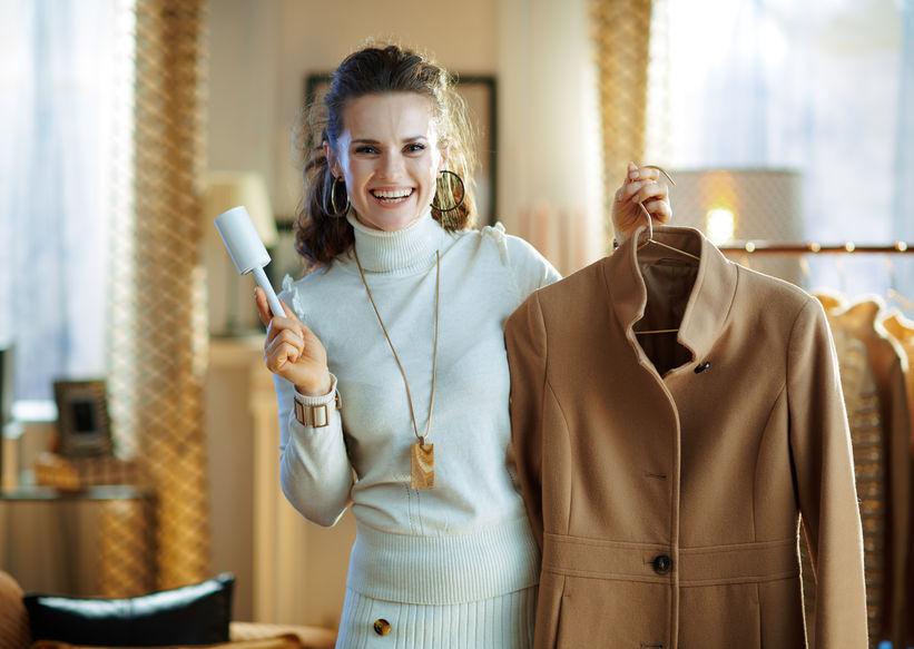 Mulher elegante e sorridente limpando casaco em cabide com rolo de fiapos