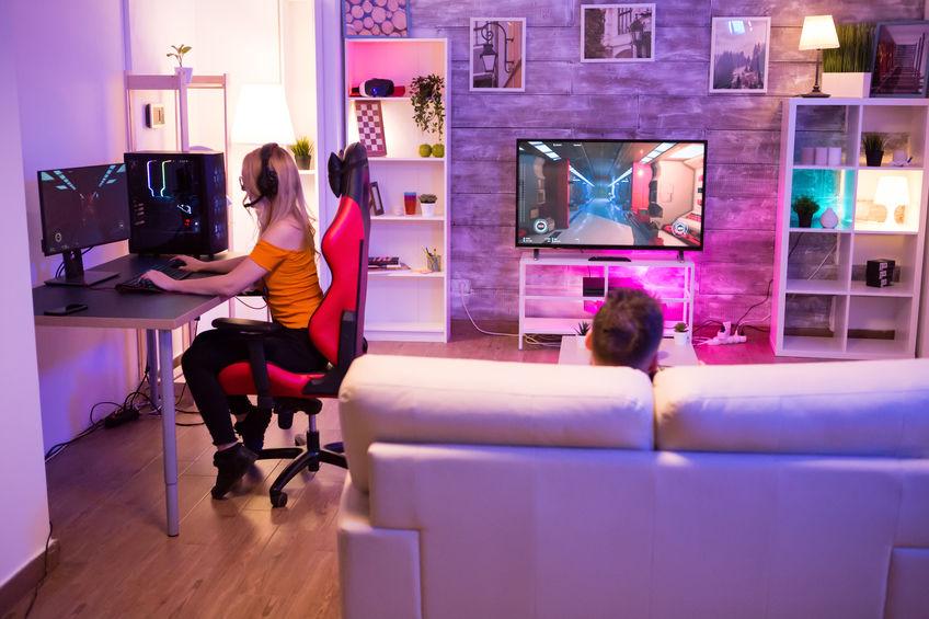 Rapariga loira jogando jogos de tiro em uma sala com luz de néon
