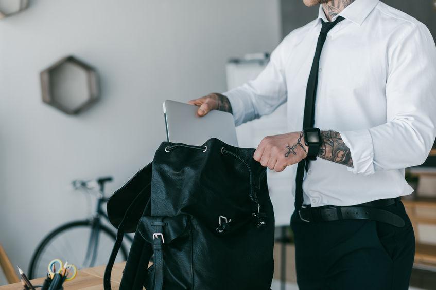 foto recortada de jovem empresário tatuado colocando laptop na mochila