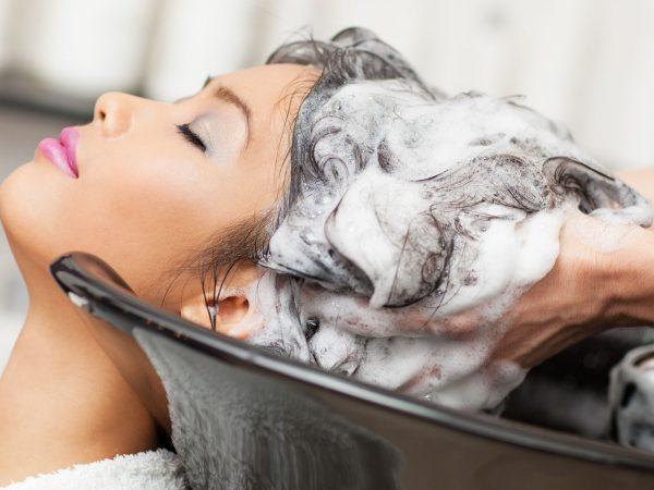 estilista lavando o cabelo de uma menina