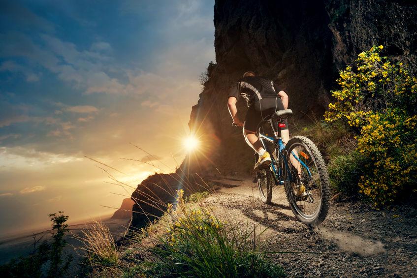 menino na montanha com bicicleta
