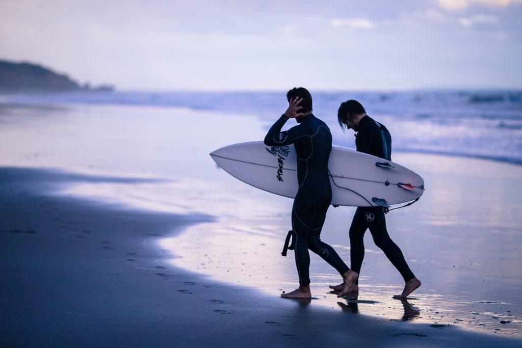 dois homens surfando na praia gelada