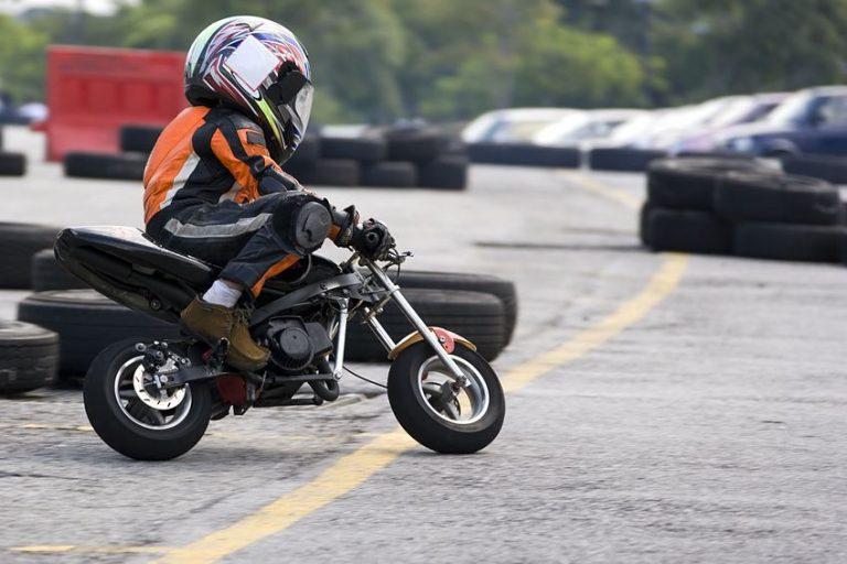 menino dirigindo uma mini motocicleta