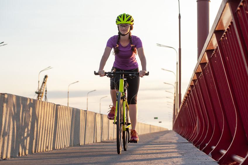 garota andando de bicicleta em uma ponte