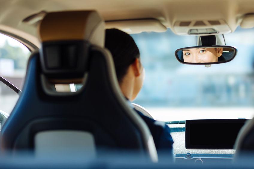 mulher olhando no espelho retrovisor