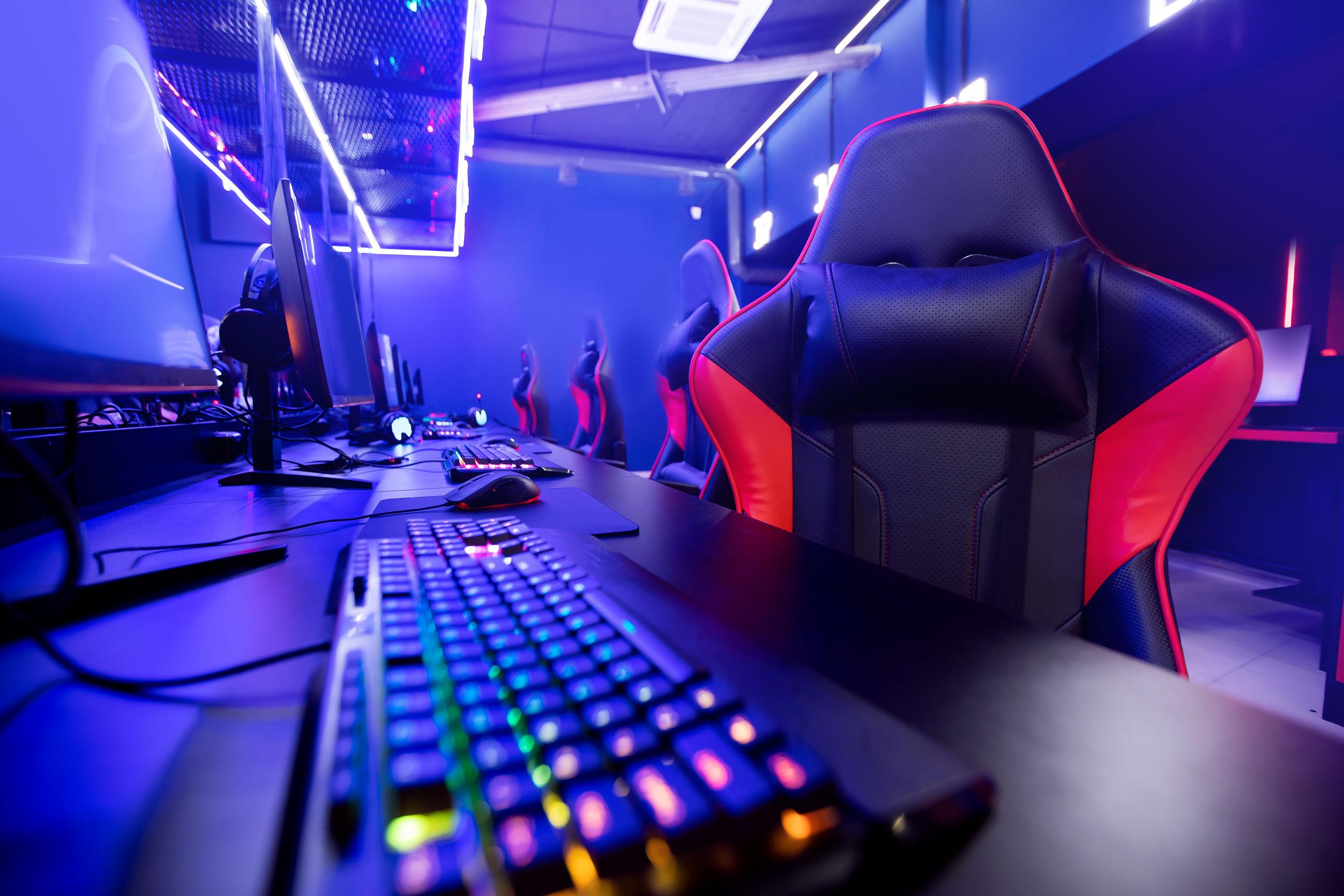 Sala com diversas estações gamers, compostas por: cadeira gamer, teclado, mouse, mouse pad e monitor.