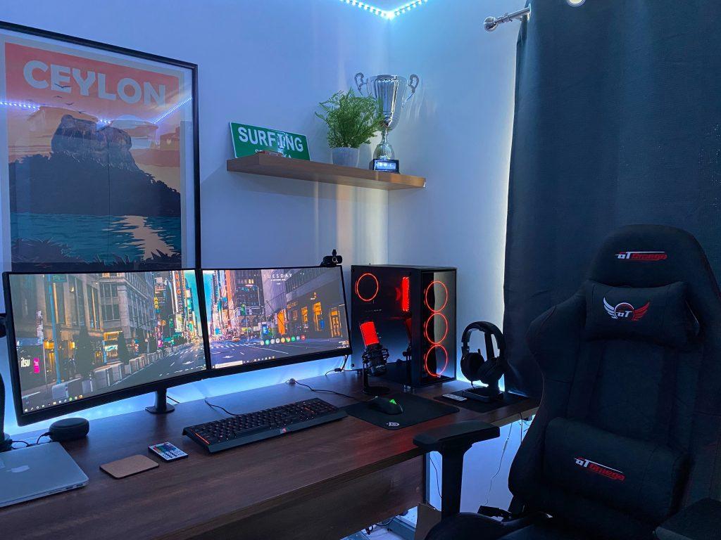 Quarto gamer com uma cadeira gamer com proteção para lombar e pescoço, dois monitores, um headset e um computador estilizado.