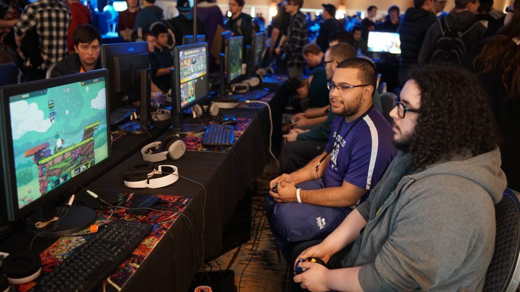 grupo de jovens jogando videogame em um campeonato online com várias pessoas em volta