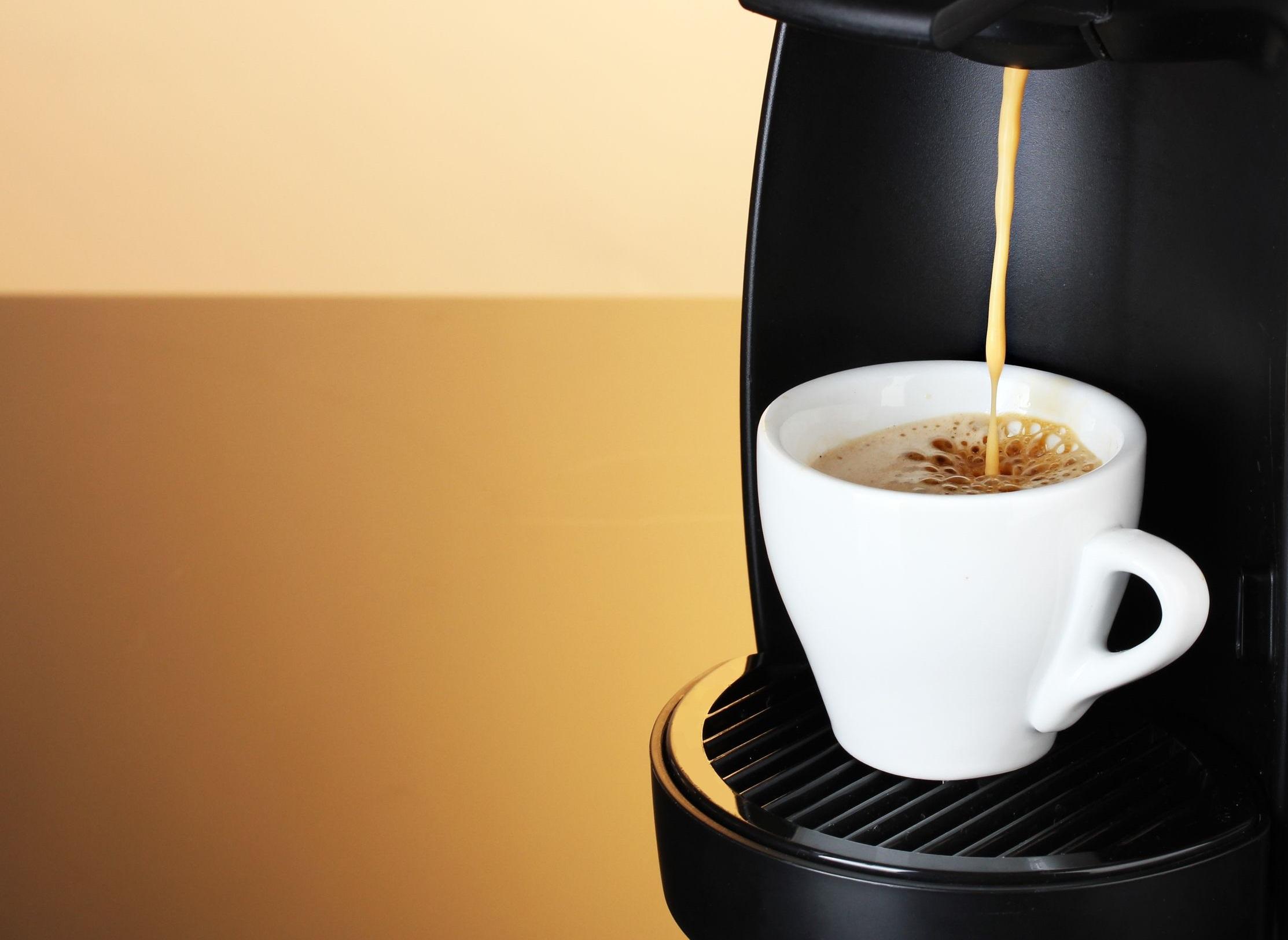 cafeteira Dolce Gusto com xícara de cappuccino em um fundo escuro