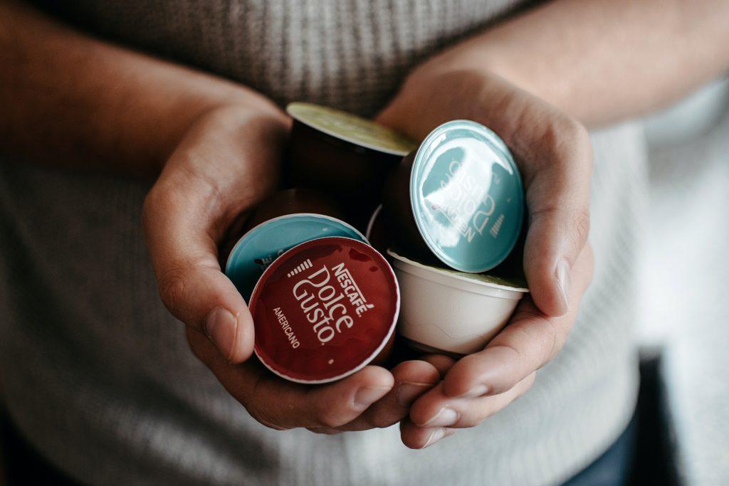 mulher com cápsulas da cafeteira Dolce Gusto nas mãos