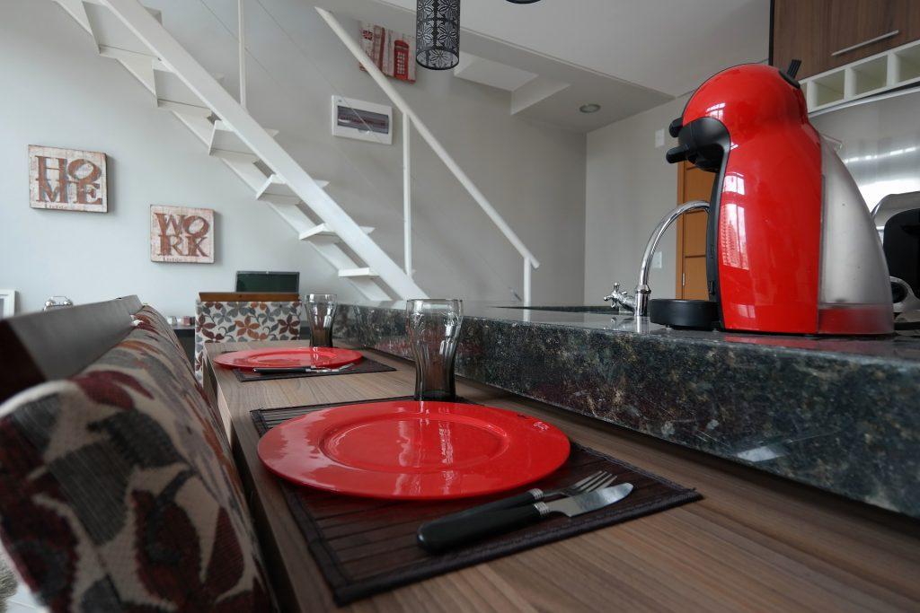 Cafeteira Dolce Gusto vermelha em uma bancada combinando com a decoração da casa.