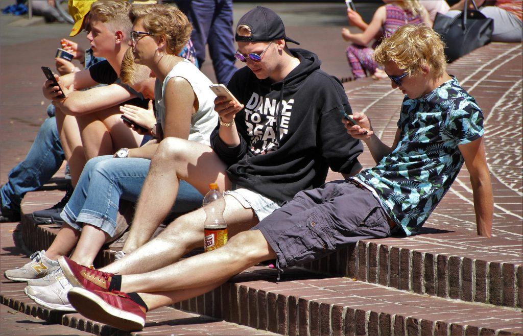 Imagem mostra um grupo de jovens jogando juntos no celular.
