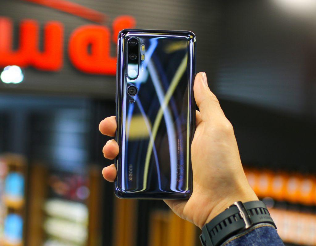 Imagem mostra uma mão segurando um celular Xiaomi em frente a uma loja.