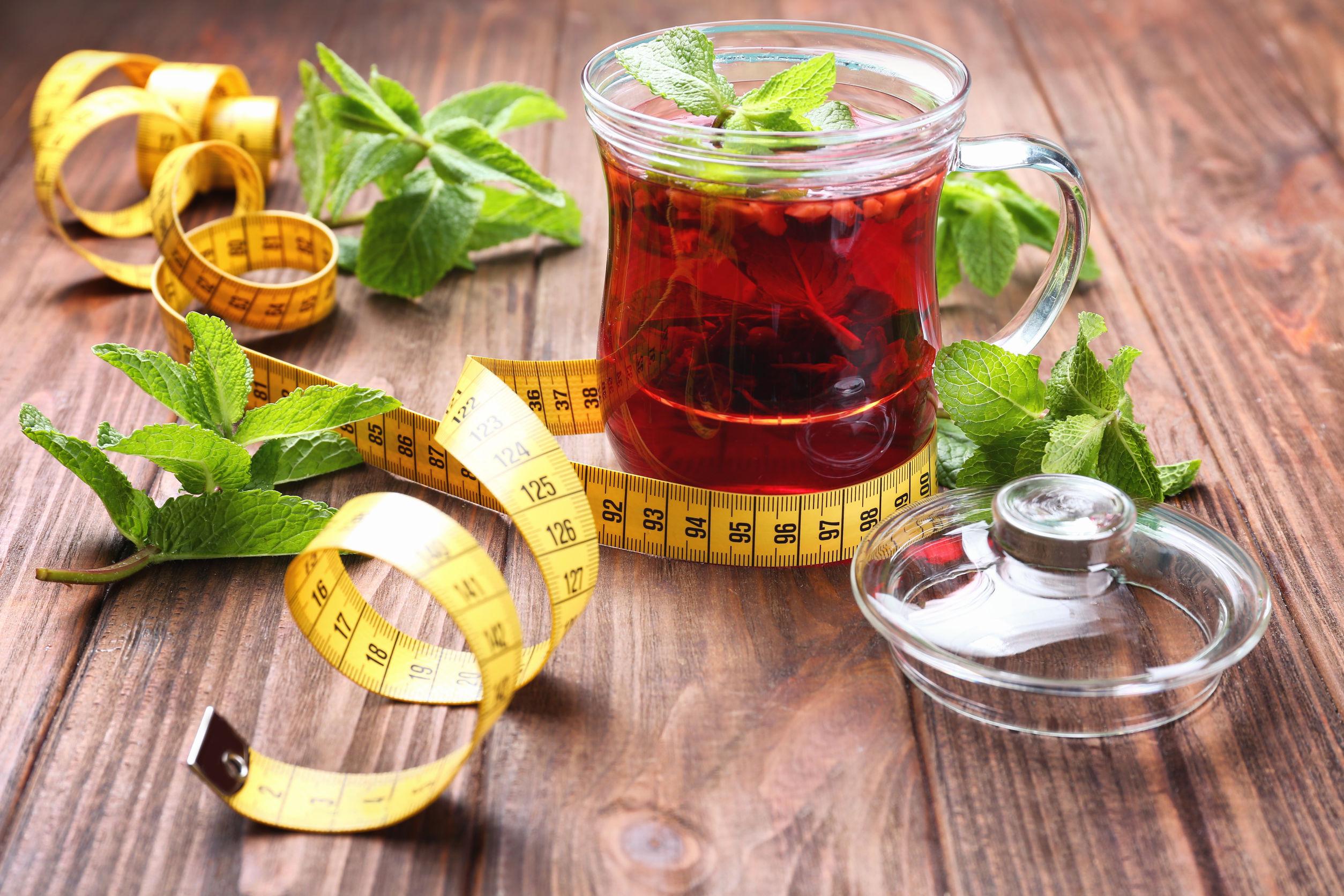 xícara com chá para emagrecer, folhas de hortelã e uma fita métrica