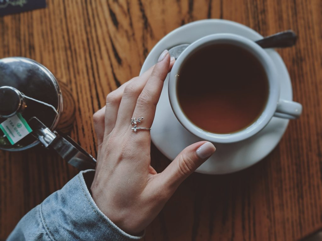 Mão de uma mulher segurando uma xícara de chá para emagrecer
