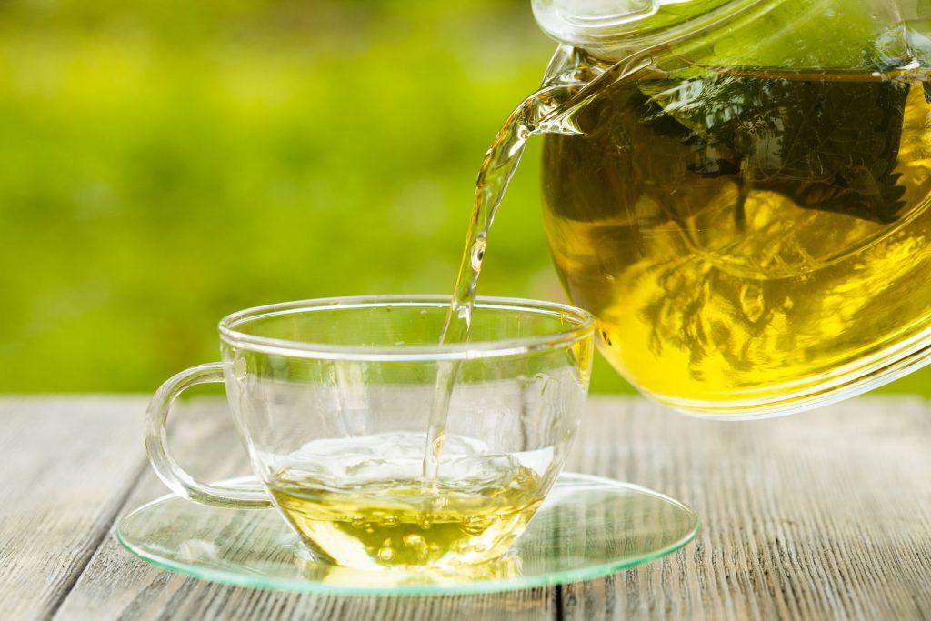 chá para emagrecer sendo servido em uma xícara com paisagem natural ao fundo