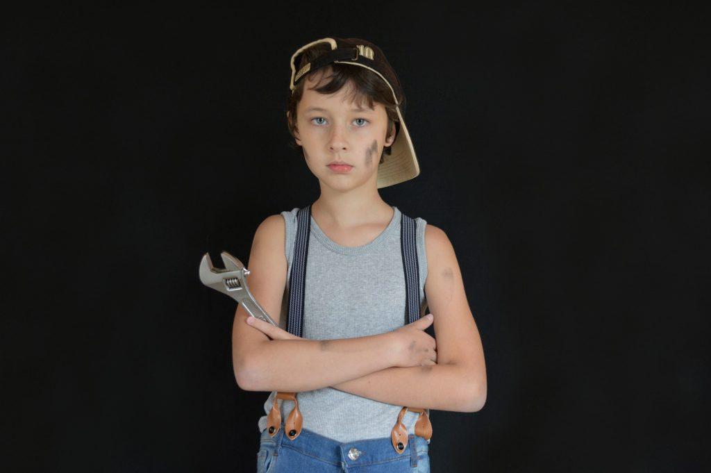 Imagem mostra uma criança segurando uma chave inglesa.