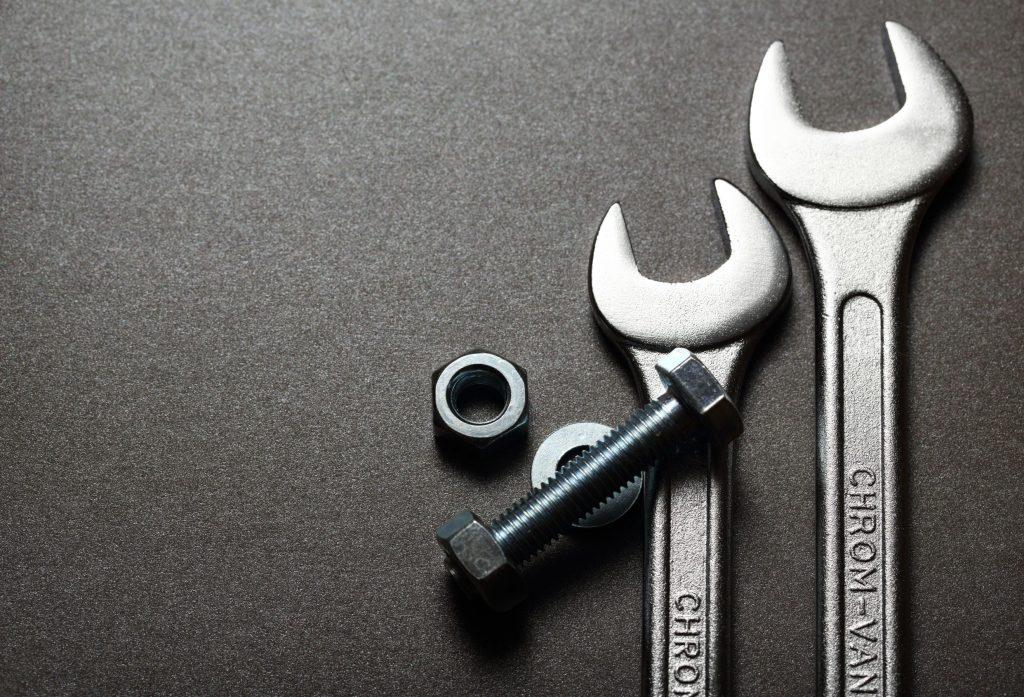 Imagem mostra uma chave inglesa junto a outras ferramentas essenciais.