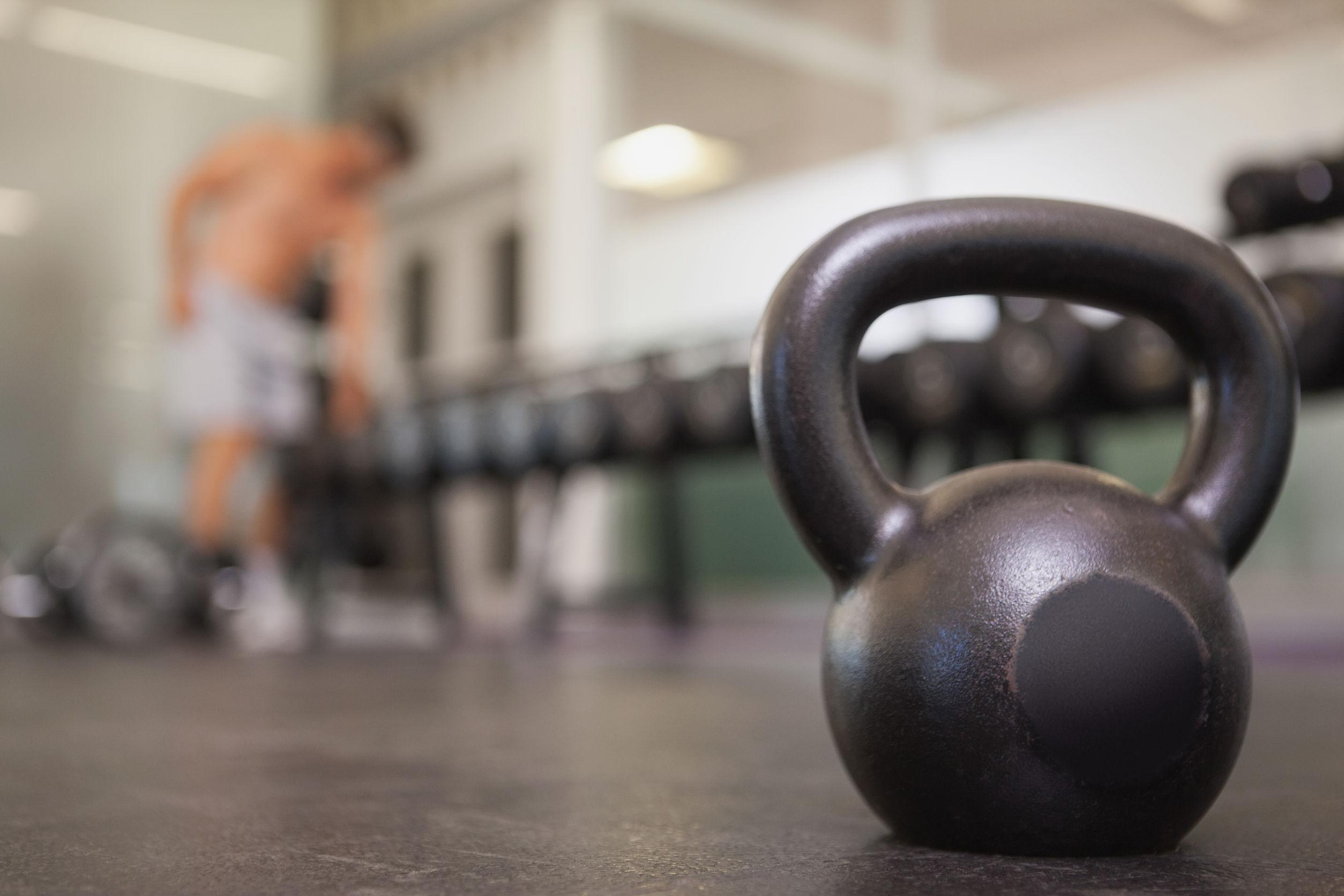 Imagem de um kettlebell no chão de uma academia com um homem desfocado ao fundo