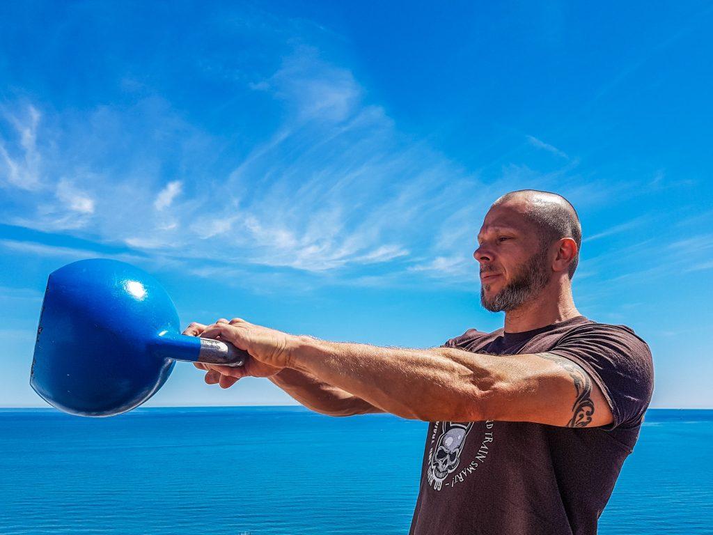 Homem careca e de barba praticando exercício físico segurando um kettlebell azul, com o mar de fundo