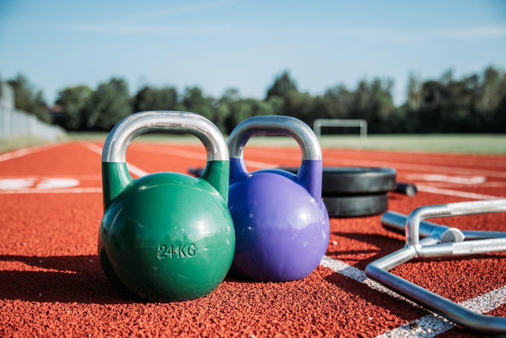 Dois kettlebells, um verde e um roxo, junto com outros equipamentos de academia mais ao fundo, em uma pista de atletismo