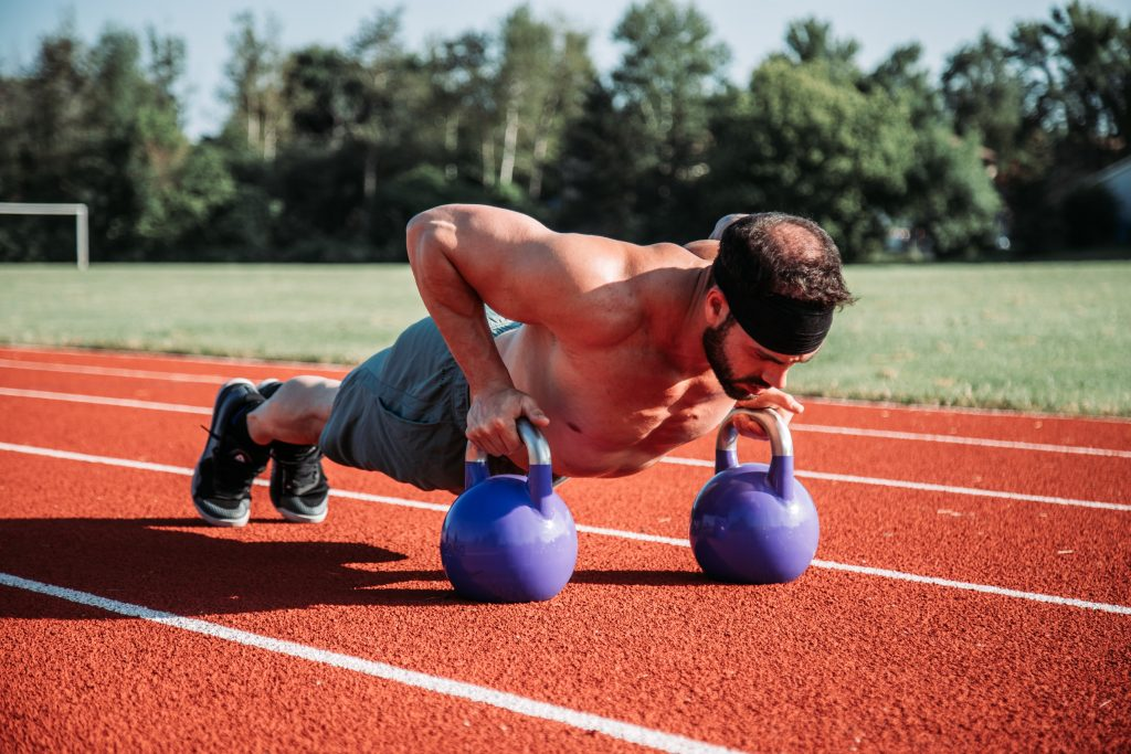Dois kettlebells, um verde e um roxo, em uma pista de atletismo com equipamentos de atividade física em volta ao fundo.