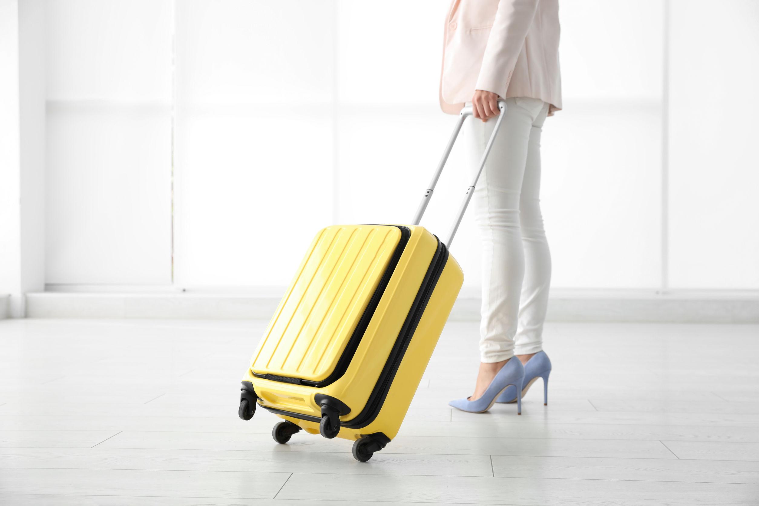 pessoa carregando uma mala de bordo amarela