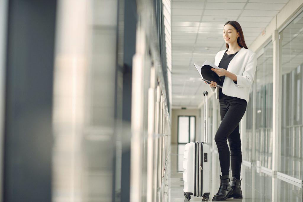 mulher jovem no corredor do aeroporto com mala de bordo branca