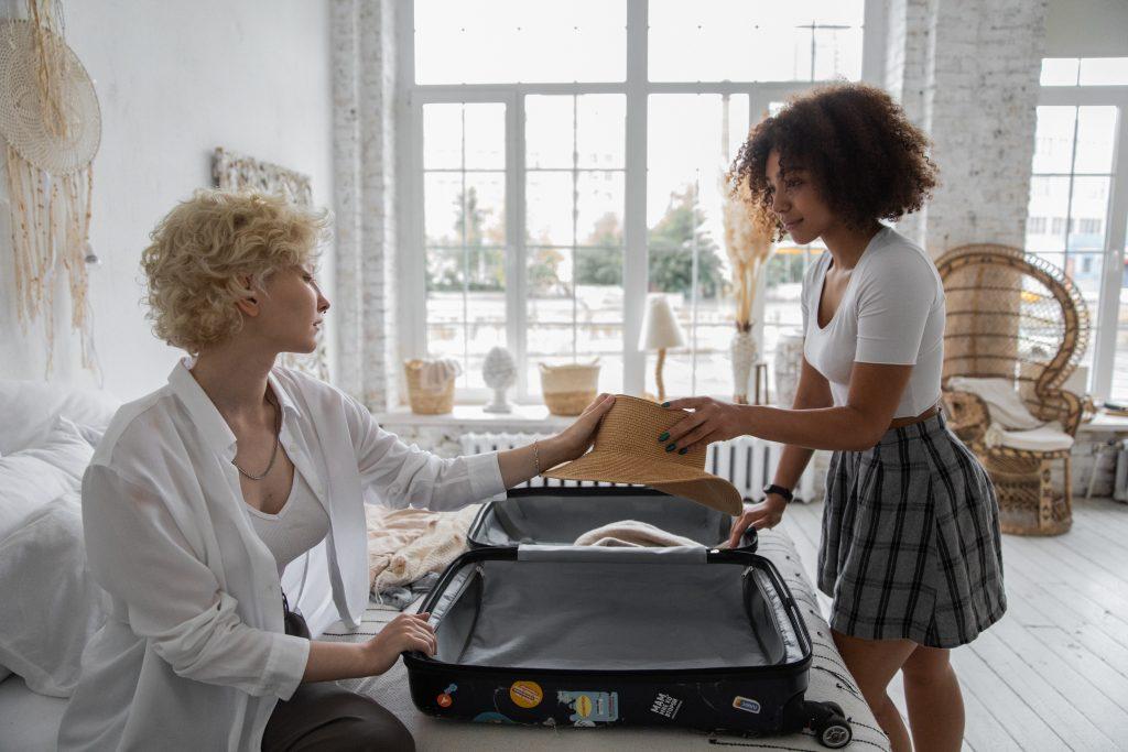 duas mulheres começando a organizar a bagagem em uma mala de bordo