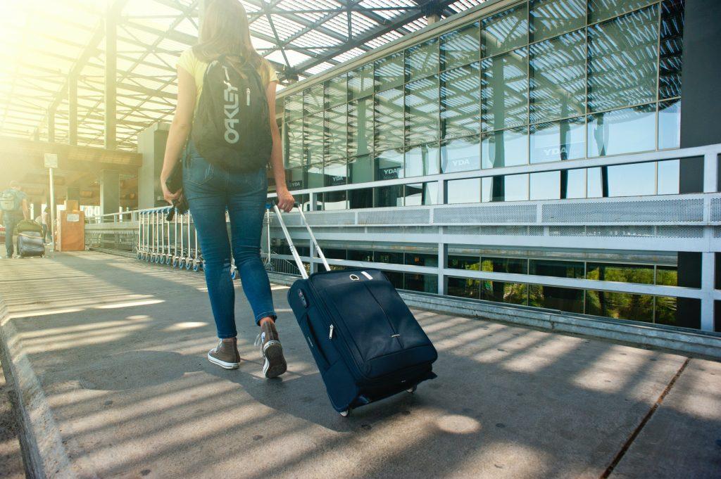 moça caminhando pelo aeroporto com uma mala de bordo e mochila nas costas