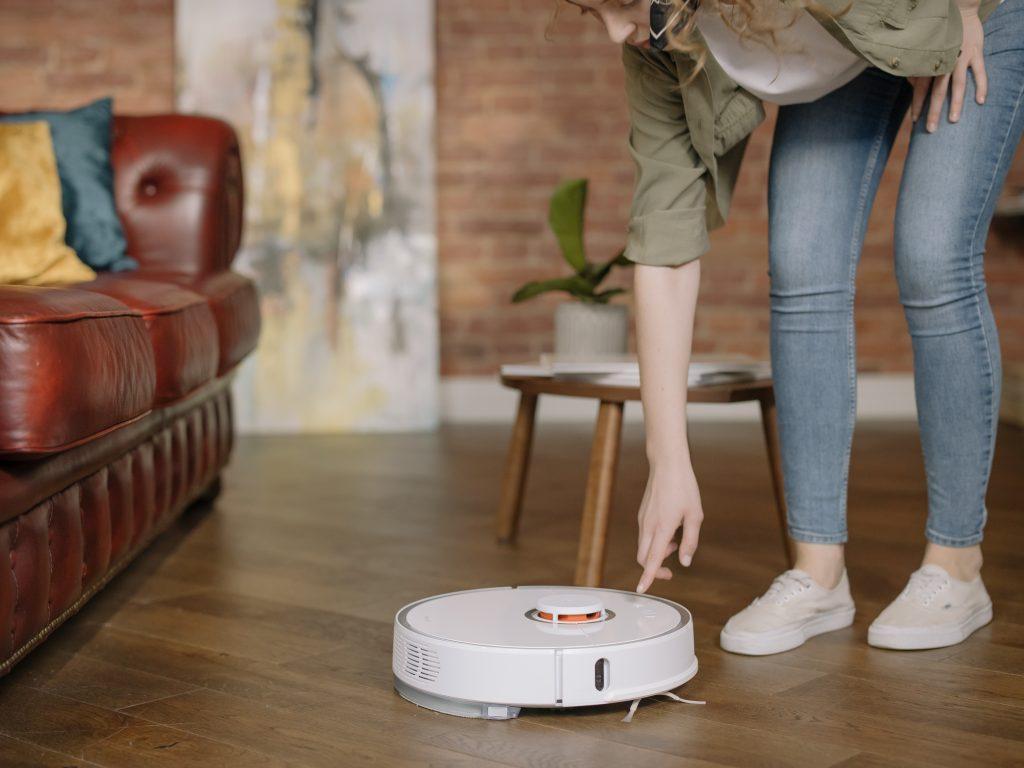 Na foto está uma mulher apertando o botão de um aspirador de pó robô.