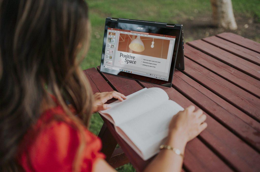 Imagem de uma mulher utilizando um notebook conversível.