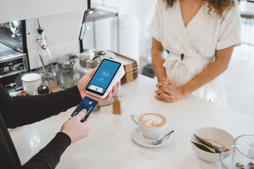 Mulher pagando o café que acabou de comprar com o cartão de crédito
