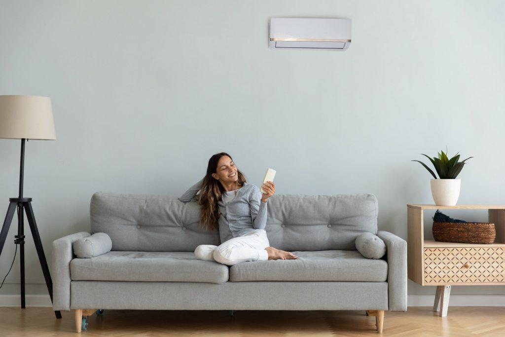 mulher na sala ligando o aparelho de ar condicionado