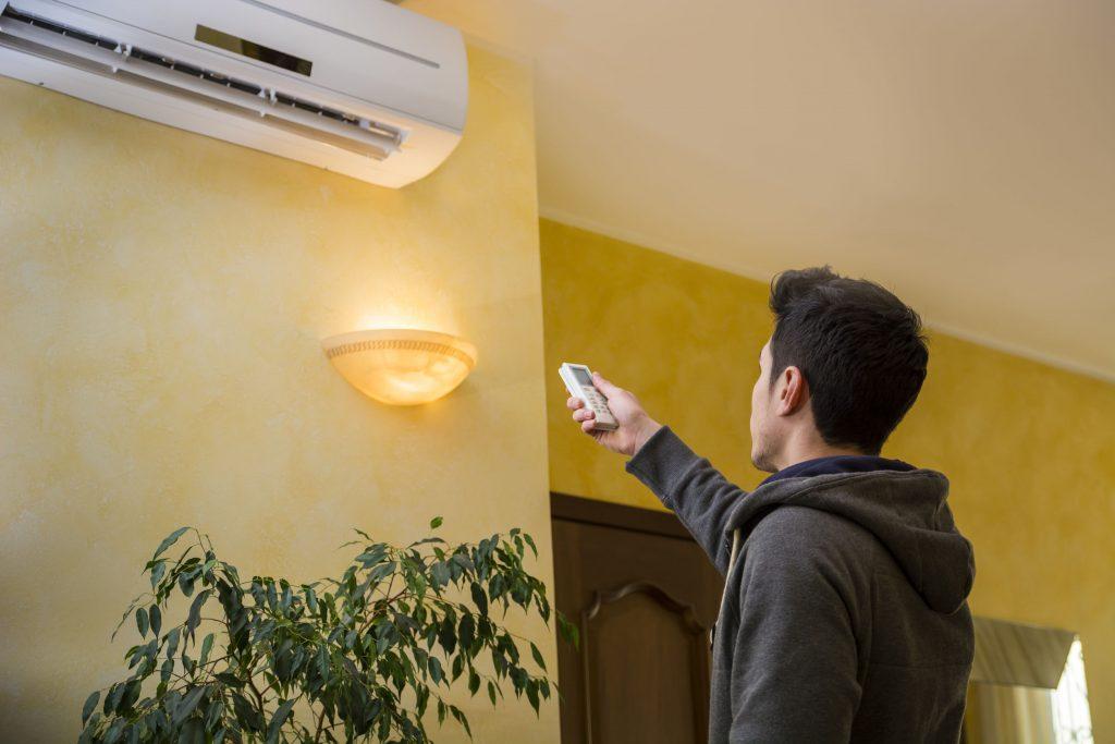 rapaz controlando o aparelho de ar condicionado na sala
