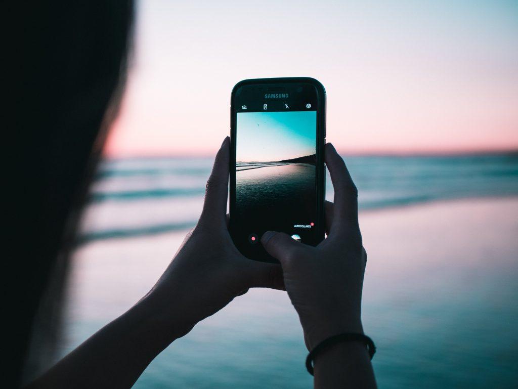 Imagem uma pessoa fotografando o mar de noite com um smartphone