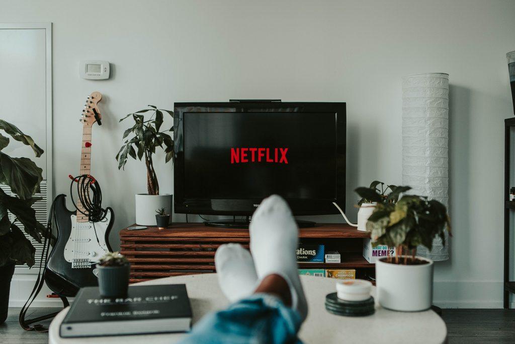Imagem mostra pés sobre centro de mesa de sala com TV no Netflix ao fundo