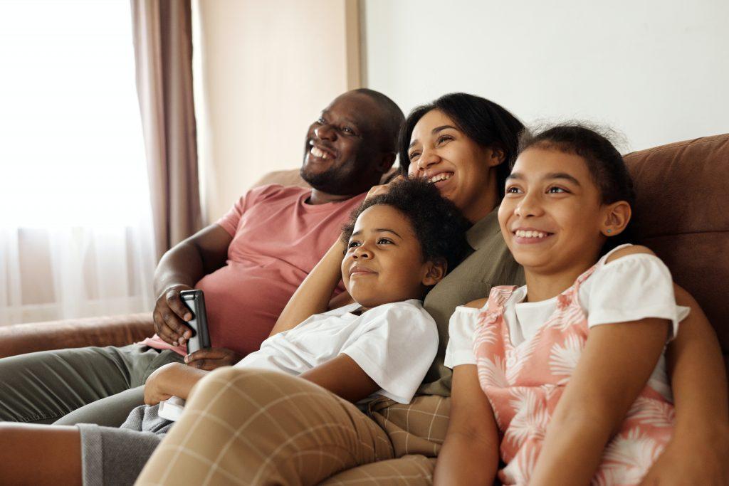 Imagem mostra família feliz no sofá assistindo TV