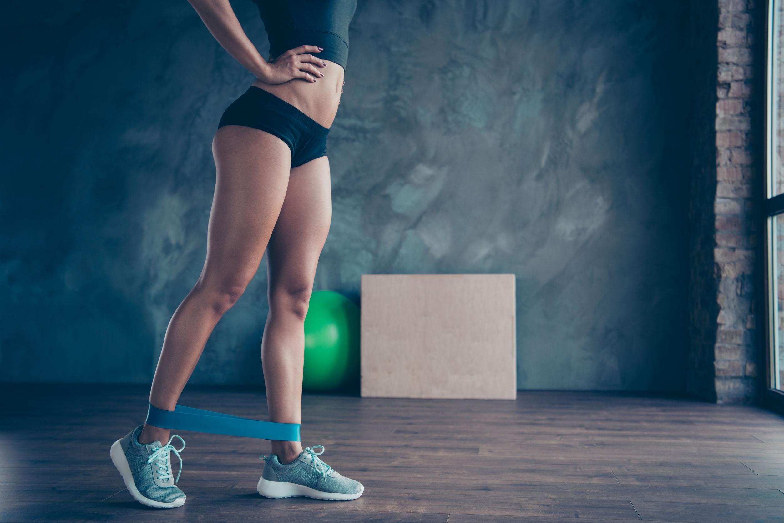 Mulher praticando exercícios com uma mini band na altura das canelas
