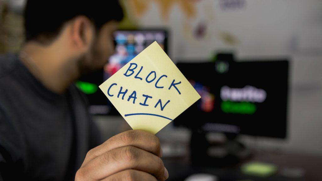 Homem segura na mão um papel escrito Block Chain