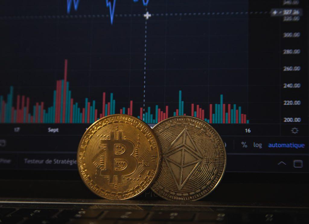 Moedas de Bitcoin em frente a uma tela de computador que exibe volume de negociações e gráfico financeiro