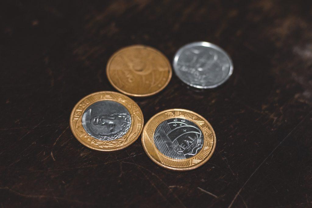 Duas moedas de um real, uma de cinquenta centavos e outra de 25 centavos.