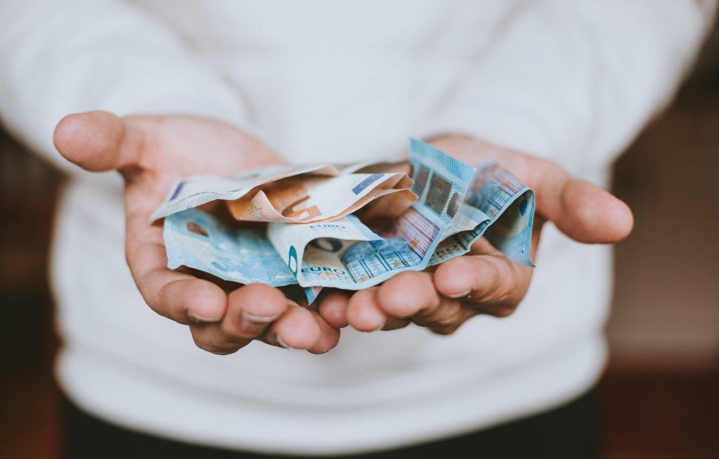 Duas mãos abertas seguram notas de dinheiro
