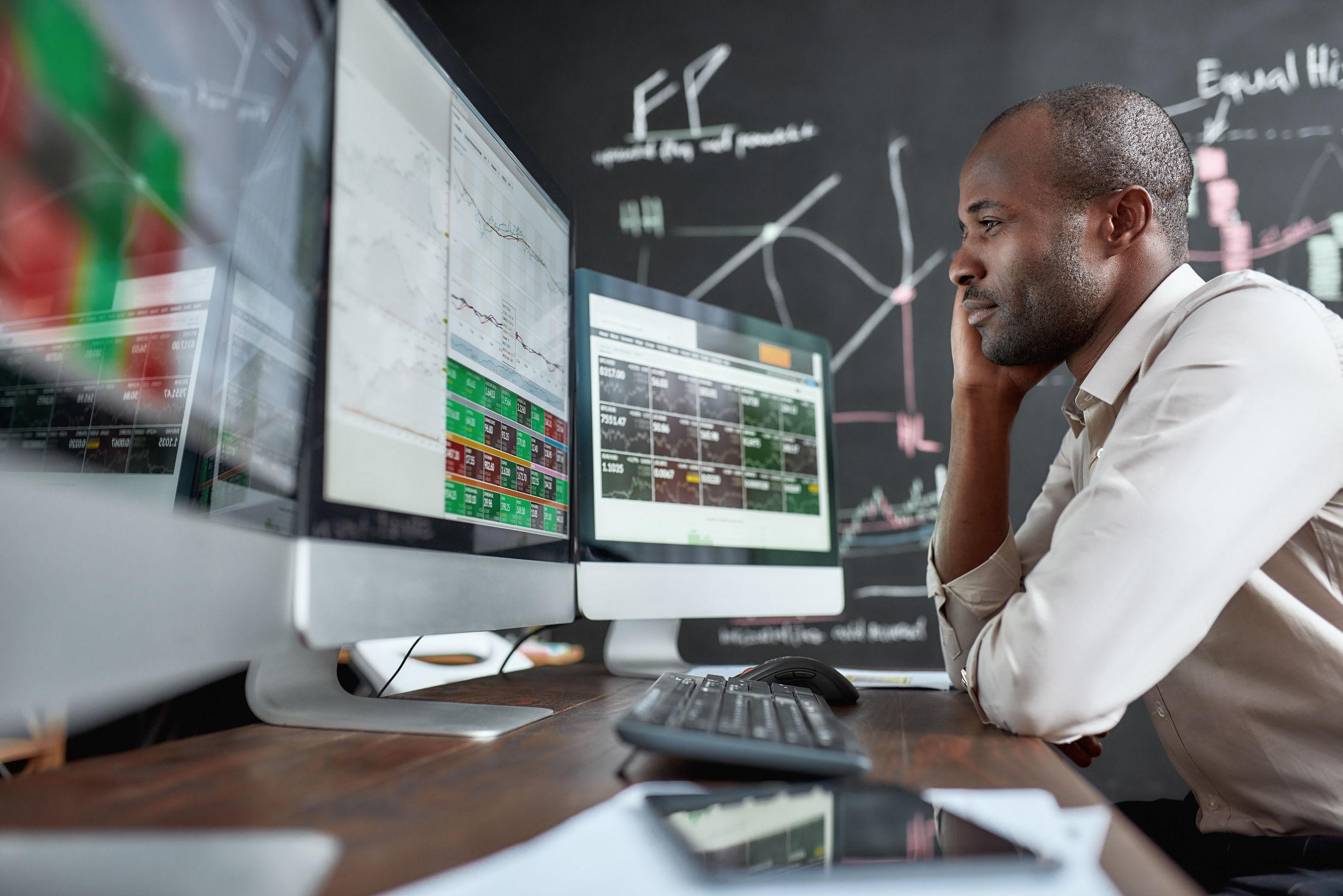 Homem em frente ao computador olhando para gráficos de ações