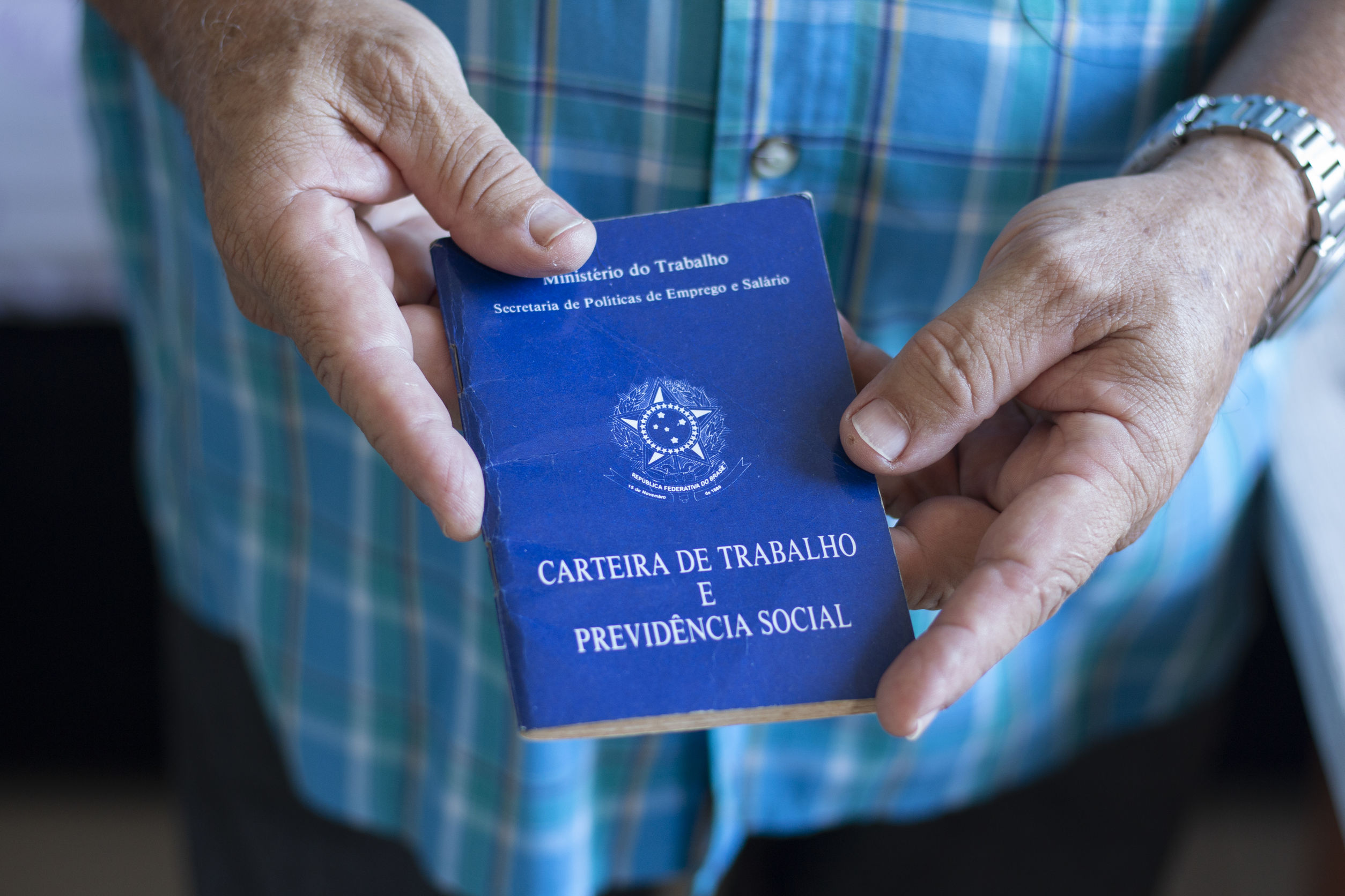 Homem segurando carteira de trabalho