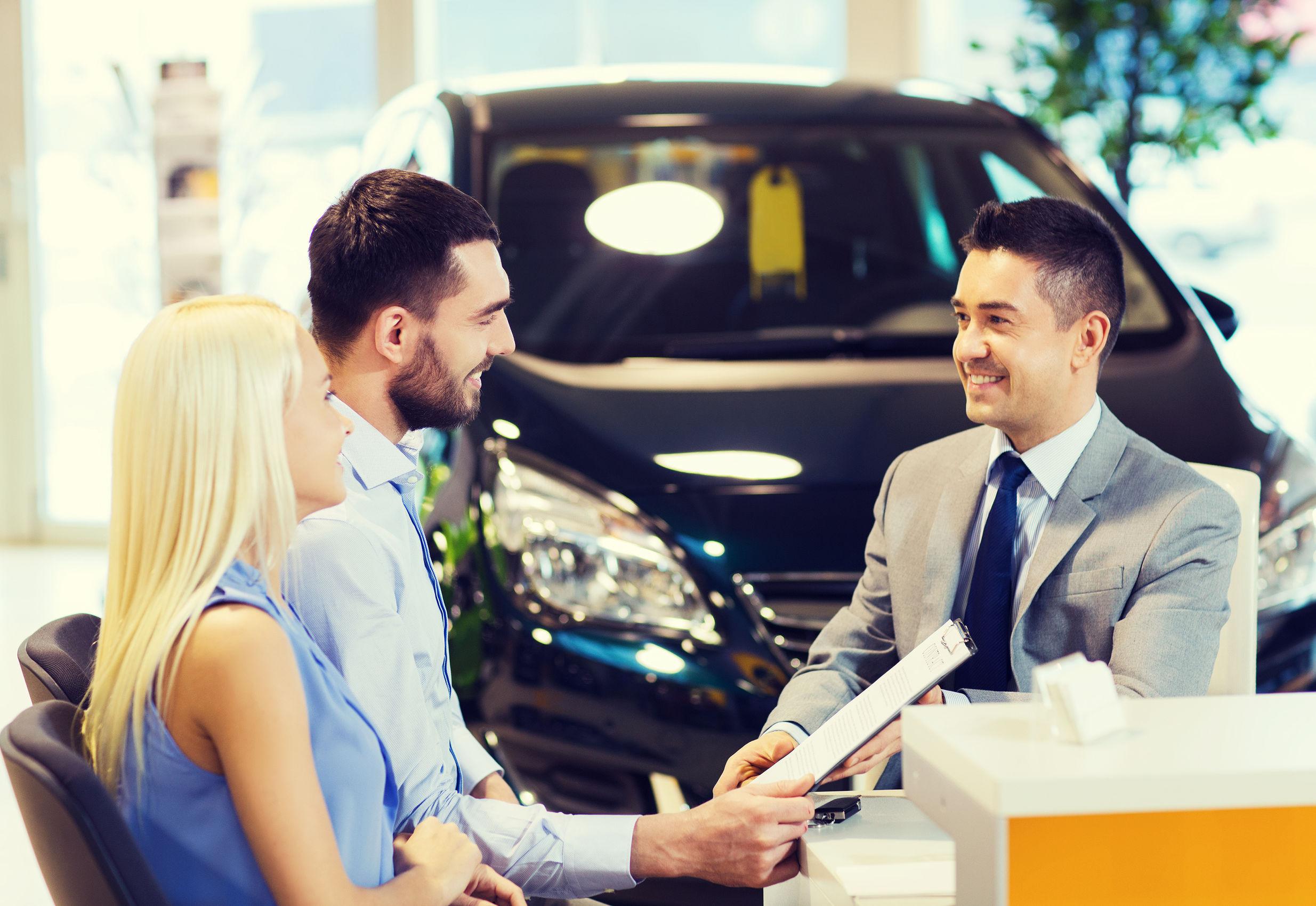Casal assinando o contrato para a compra de um carro