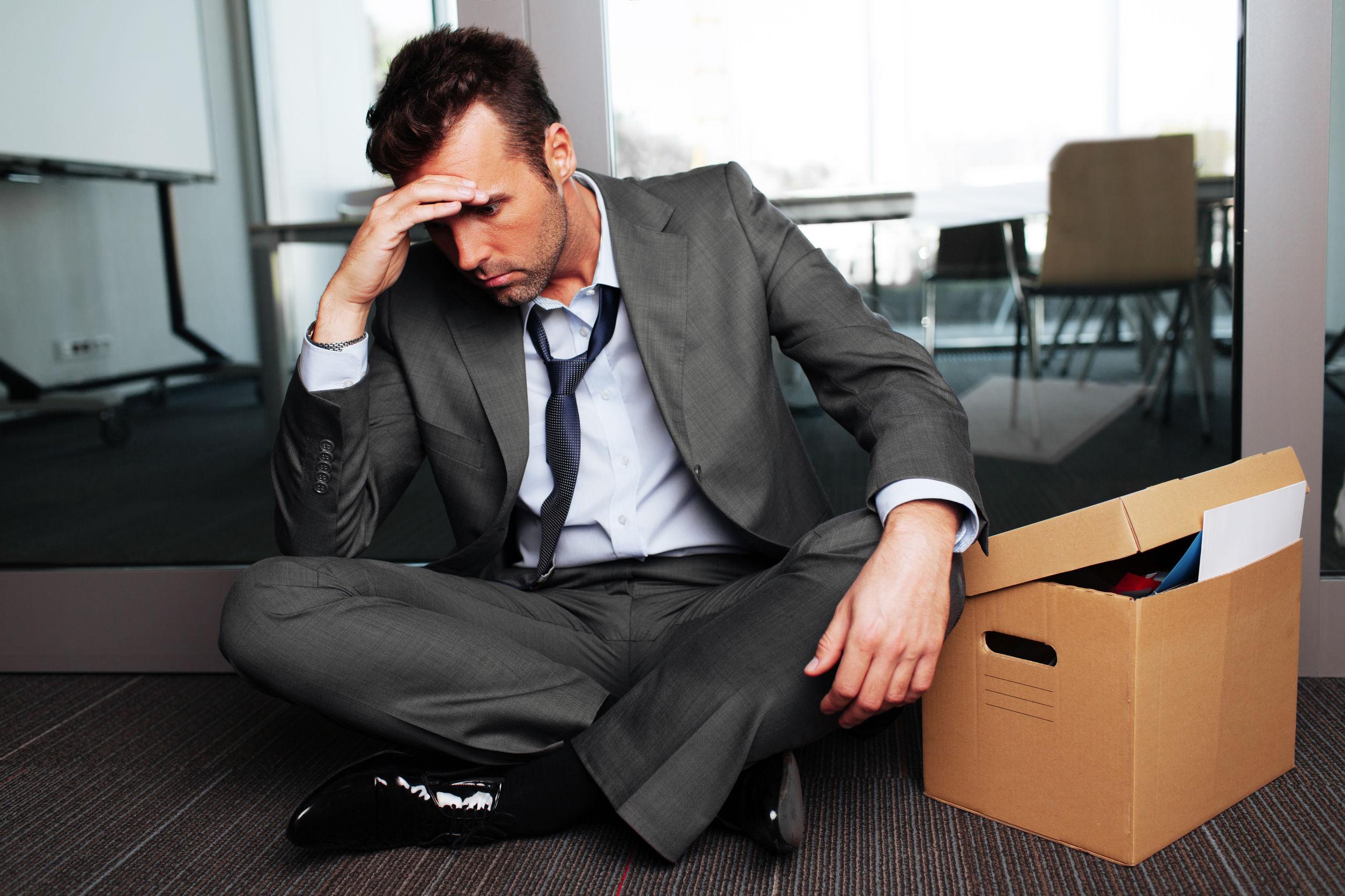 A foto mostra um homem recém demitido sentado no chão da empresa com uma caixa de pertences ao lado